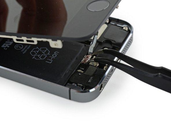 بعد از تعویض ویبراتور آیفون 5S (موتور ویبره) و زمانی که نوبت به جا زدن براکت دکمه هوم گوشی میرسد باید از یک قلق خاص استفاده کنید. ابتدا براکت مذکور را مثل عکس با پنس بگیرید. پنس باید لبه های عرضی براکت را نگه داشته و له طولی دورتر آن رو به سمت پایین شیب داده شود.