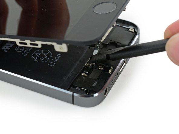 نوک اسپاتول را روی براکت دکمه هوم (تاچ آیدی) آیفون SE قرار دهید و با یک فشار کوتاه آن را روی برد نصب نمایید.