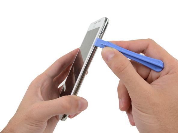 قاب باز کن را در لبه سمت راست قاب گوشی حرکت دهید و به گونهای اهرم کنید که این بخش از قاب گوشی کاملا شل گردد.