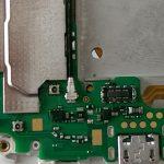 پیچی که در عکس اول نشان داده شده و به نوعی نگهدارنده برد ثانویه اسند جی 7 تعمیری است را از لبه زیرین قاب گوشی جدا کنید.