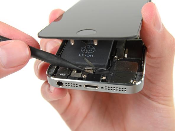 نوک اسپاتول یا پنس را مثل عکس در گوشه کانکتور دکمه هوم آیفون SE تعمیری قرار دهید و آن را باز کنید.