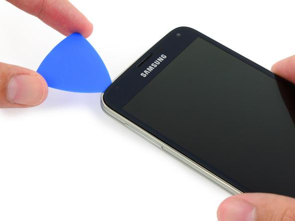 پیک را در گوشه فوقانی و سمت چپ قاب Galaxy S5 تعمیری بچرخانید تا مسیر حرکتش تغییر کرده و به لبه سمت چپ قاب گوشی هدایت شود.