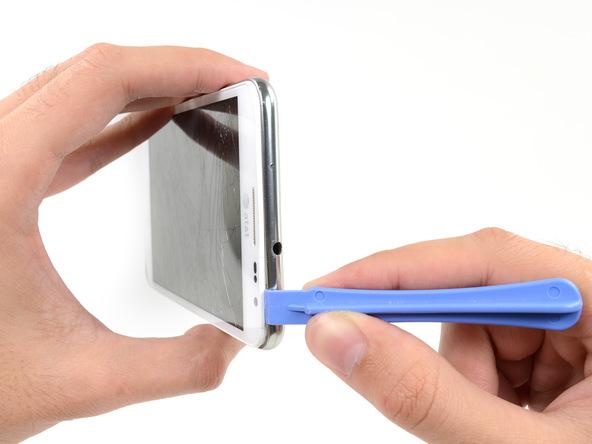 قاب باز کن را از لبه سمت راست به لبه فوقانی قاب گوشی منتقل کرده و این بخش از قاب گلکسی نوت تعمیری را هم شل نمایید.