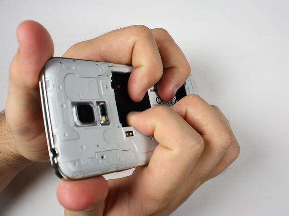 گلکسی اس 5 مینی تعمیری را مثل عکس اول در دستتان بگیرید. دقت کنید که انگشت اشاره و میانی دو دست شما باید در مکانی از بدنه گوشی قرار بگیرند که باتری روی آن سوار میشود. دو انگشت شست خود را هم در لبه های فوقانی قاب گوشی قرار دهید.