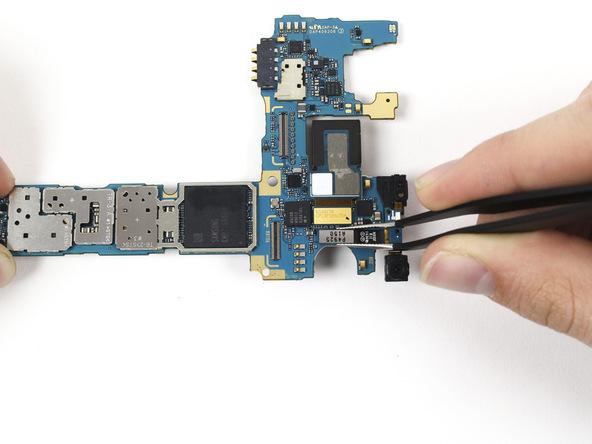 مادربرد گلکسی نوت 4 تعمیری را سر و ته کنید و بخش فلزی که در عکس دوم مشخص است را با پنس گرفته و به سمت بالا بکشید تا آزاد شود.