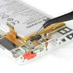 لبه دومین چسب زیر باتری را هم با نوک پنس گرفته و به سمت عقب بکشید تا کمی از زیر باتری گوشی آزاد شده و جای دست کافی برای گرفتن آن ایجاد گردد.