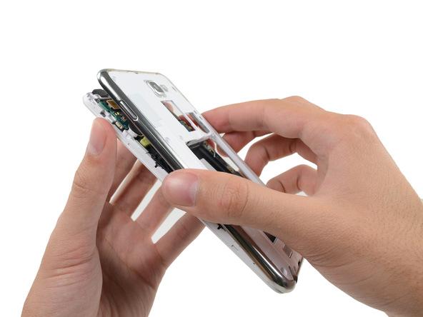 گلکسی نوت تعمیری را به گونهای که در عکس اول نشان داده شده در دستتان بگیرید و با فریم میانی آن را از بدنه جدا کنید.