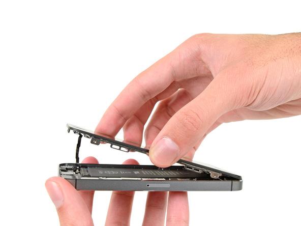 حال که اتصالات قاب لبه زیرین آیفون SE کاملا از بین رفته است، میتوانید گوشی را روی میز کارتان قرار دهید و به آرامی پنل جلوی آن را از لبه زیرین به سمت لبه فوقانی (به صورت کتابی) باز کنید. دقت کنید که به لبه فوقانی آیفون SE هیچ نیرویی وارد نمیشود و این بخش مثل یک لولا عمل میکند. پنل جلوی آیفون SE تعمیری را تا جایی باز کنید که نسبت به پنل پشت آن زاویه 90 درجه پیدا کند.