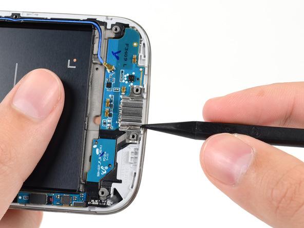 روی سوکت شارژ Galaxy S4 تعمیری یک براکت خاص و فنری نصب است. نوک اسپاتول را زیر لبه سمت راست این براکت فرو برده و آن را به سمت بالا هول دهید تا از روی سوکت شارژ گوشی بلند شود.