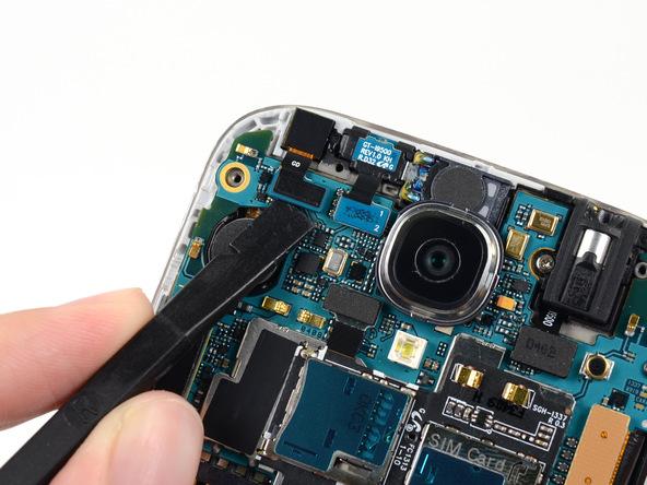 نوک پهن اسپاتول را زیر کانکتور دوربین سلفی Galaxy S4 تعمیری قرار داده و آن را از روی برد باز کنید.