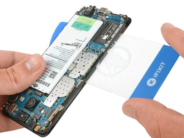 گلکسی A3 2016 تعمیری را روی میز کارتان قرار دهید یا مثل عکس اول در دستتان بگیرید. به آرامی یک قاب زا کن کارتی را از سمت راست به مابین ال سی دی و فریم آن فرو ببرید و سعی کنید فریم ال سی دی را کاملا از روی LCD بلند کنید.
