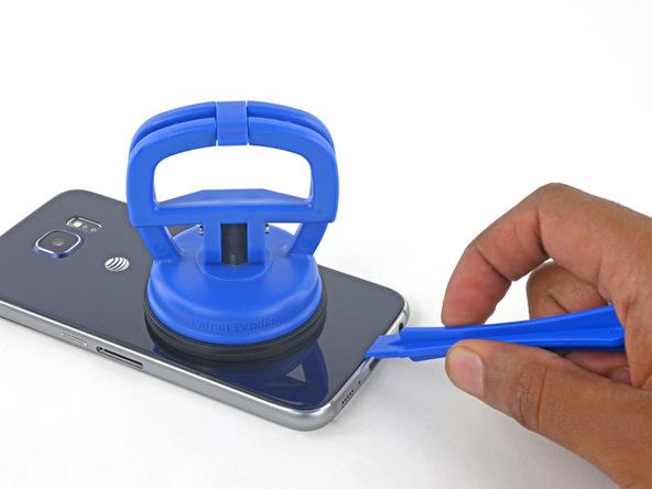 گلکسی اس 6 تعمیری را روی میز کارتان قرار دهید. با نوک قاب باز کن یا اسپاتول لبه زیرین بدنه اصلی گوشی را نگه دارید و با دست دیگرتان ساکشن کاپ را به سمت بالا بکشید. شدت نیروی کششی را به تدریج تا جایی افزایش دهید که لبه زیرین درب پشت گلکسی اس 6 تعمیری از روی بدنه آن بلند شود.