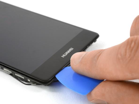 نوک پیک را به آرامی از لبه زیرین قاب گوشی به داخل شکاف مابین بدنه و ال سی دی هوآوی P9 Plus فرو ببرید و در این بخش از قاب گوشی به صورت رفت و برگشت حرکت دهید تا کاملا شل شود.