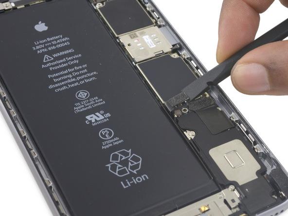 کانکتور باتری آیفون 6 اس پلاس تعمیری را با نوک اسپاتول خیلی آرام به سمت چپ هول دهید تا کاملا از سوکت روی برد فاصله بگیرد. انجام این کار سبب میشود تا از قرار گرفتن احتمالی کانکتور باتری روی سوکت و انتقال انرژی به قطعات سخت افزاری گوشی در طی تعمیر آن جلوگیری شود.