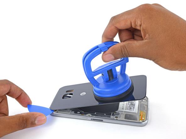 پیک را مجددا در شکاف لبه فوقانی درب پشت گلکسی اس 6 فرو کرده و با آن بازی کنید تا باقی ماندههای لاستیک آب بندی این قسمت از بین بروند و درب پشت گوشی کاملا آماده جداسازی شود.