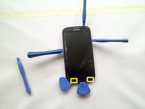 دو پیک را از لبه زیرین قاب Galaxy S3 تعمیری به داخل شکاف مابین ال سی دی و گلس روی آن فرو ببرید و پیک ها را در همان قسمت رها سازید.
