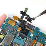 براکت روی دوربین سلفی و جک هدفون گلکسی نوت تعمیری را با پنس گرفته و از آن جدا کنید.