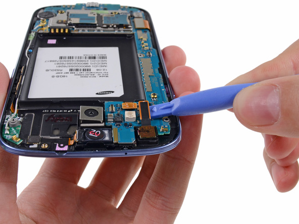 کانکتور دوربین سلفی Galaxy S3 تعمیری را با نوک اسپاتول از روی برد باز کنید.