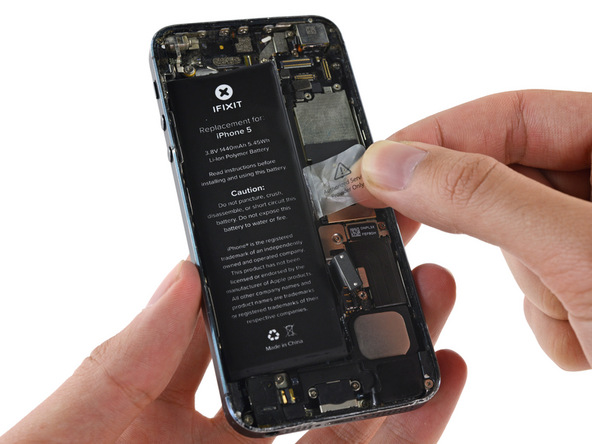 لاستیک کوچکی که در لبه سمت راست باتری آیفون 5 واقع شده را با انگشت گرفته و به سمت بالا بکشید تا باتری گوشی از درب پشت آیفون بلند شود.