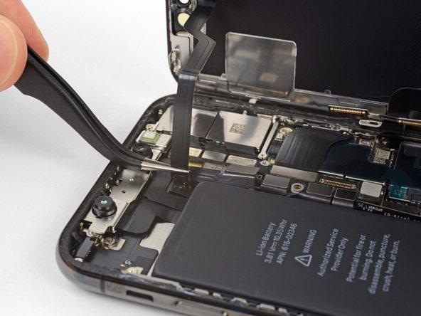 سیم سنسورهای جلوی آیفون X تعمیری را با نوک پنس گرفته و به آرامی سعی کنید آن را از روی برد گوشی بلند نمایید. این سیم با چسب های خاصی روی برد نصب شده است. بعد از اینکه سیم از روی برد جدا شد، آن را به سمت چپ بکشید تا کاملا آزاد شود.