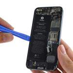 نوک اسپاتول یا قاب باز کن را در زیر باتری آیفون 5 تعمیری فرو برده و خیلی آرام آن را از روی درب پشت گوشی بلند نمایید.