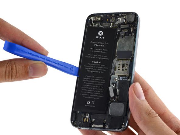نوک اسپاتول یا قاب باز کن را در زیر باتری آیفون 5 تعمیری فرو برده و آن را از درب پشت گوشی بلند کنید.