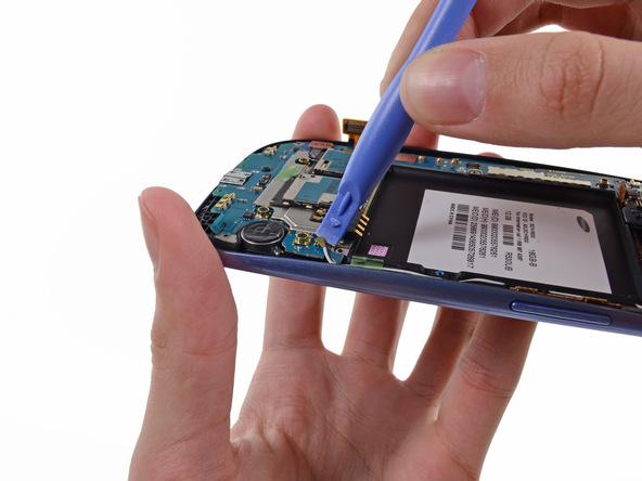 گلکسی اس 3 تعمیری را مثل عکس در دستتان بگیرید و با نوک اسپاتول خیلی آرام کانکتور فوقانی سیم آنتن وای فای گوشی را از روی برد باز کنید.