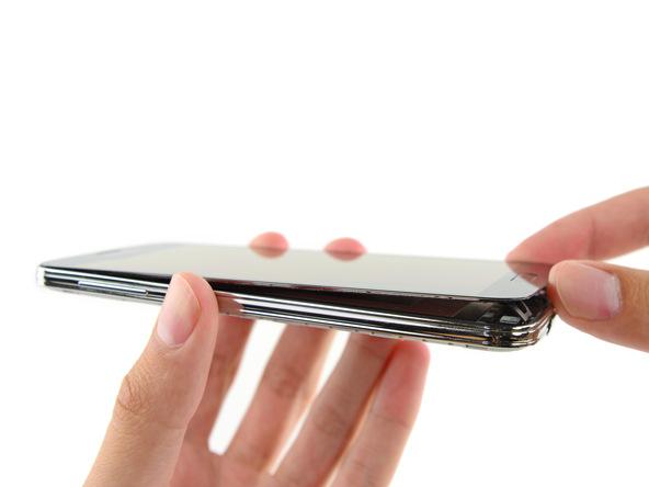 لبه زیرین نمایشگر Galaxy S5 تعمیری را با دست گرفته و به صورت کتابی باز کنید. نمایشگر را 180 درجه باز کنید و در همان حالت روی میز کارتان قرار دهید.