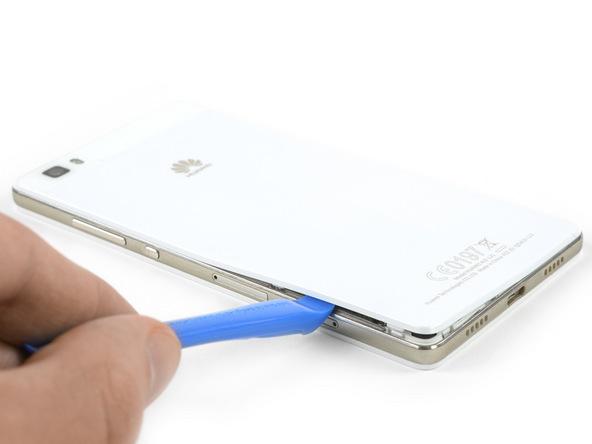قاب باز کن را از لبه زیرین قاب هوآوی P8 Lite به لبه سمت چپ آن هدایت کنید و این بخش از درب پشت گوشی را هم کاملا شل نمایید.