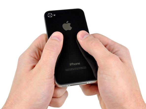 آیفون 4 تعمیری را در دستتان نگه دارید و ضمن ثابت نگه داشتن بدنه اصلی گوشی، درب پشت آن را از پایین به سمت بالا هول دهید تا لبه زیرین آن کمی از بدنه گوشی آزاد شود.