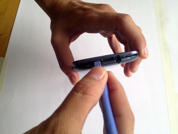 نوک اسپاتول را داخل شیار روی لبه فوقانی قاب گلکسی اس 3 تعمیری فرو ببرید و به آرامی درب پشت گوشی را از روی بدنه آن جدا کنید.