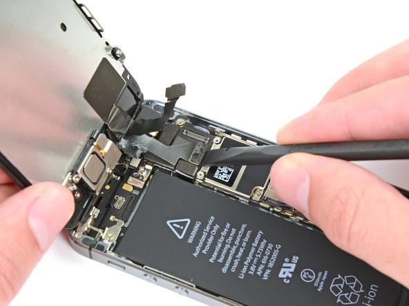 با اسپاتول، کانکتور کابل LCD آیفون SE را هم از روی پنل پشت آن جدا کنید.