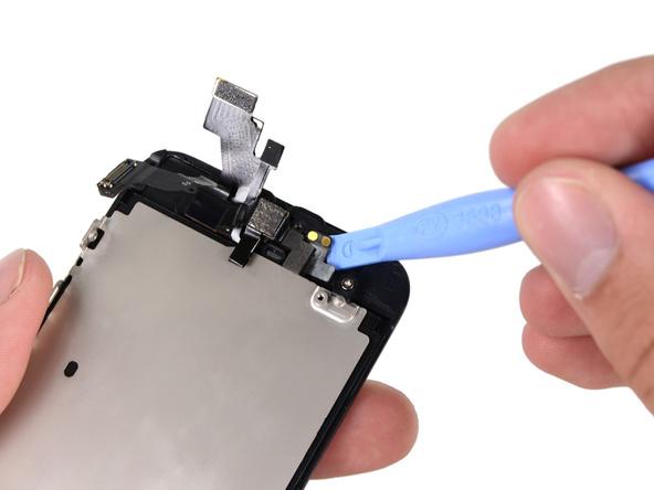 نوک اسپاتول یا قاب باز کن را خیلی آرام به زیر کنتکت اسپیکر مکالمه آیفون 5 تعمیری فرو برده ببرید.