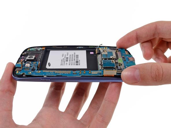 مادربرد را به سمت عقب بکشید تا کاملا از بدنه گوشی جدا گردد. از آنجایی که هدف تعویض دوربین سلفی Galaxy S3 است و این قطعه روی بدنه گوشی قرار دارد، بنابراین برد را در گوشهای امن قرار داده و ادامه تعمیر را روی بدنه Galaxy S3 دنبال کنید.
