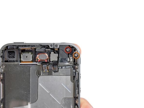 دو پیچ 6 میلیمتری و 1.4 میلیمتری که به ترتیب در عکس با رنگ قرمز و نارنجی مشخص شدهاند را باز کنید. این پیچ ها نگهدارنده موتور ویبره آیفون 4 هستند.