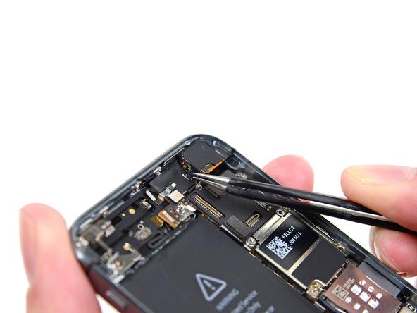 نوک اسپاتول را در داخل لبه زیرین باتری فرو برده و حرکت دهید تا لبه چسب نگهدارنده باتری گوشی مشخص شود.