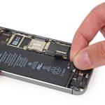 آیفون SE تعمیری را روی میز کارتان قرار دهید و با یک دست آن را نگه دارید. با انگشت دست دیگرتان لبه یکی از چسب های نگهدارنده باتری را بگیرید.