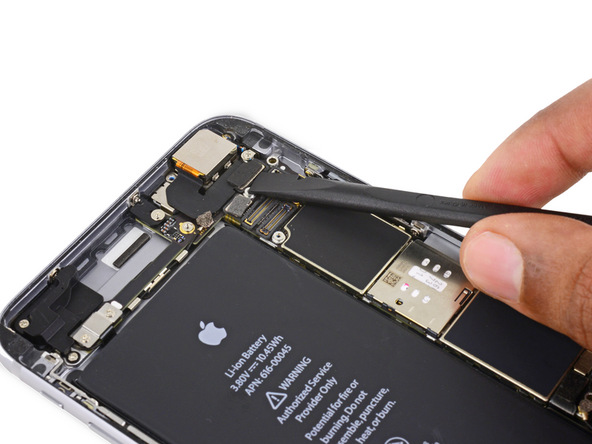 نوک پهن اسپاتول یا قاب باز کن پلاستیکی را در زیر کانکتور دوربین اصلی آیفون 6S Plus تعمیری قرار داده و آن را به سمت بالا هول دهید تا از روی برد جدا شود.
