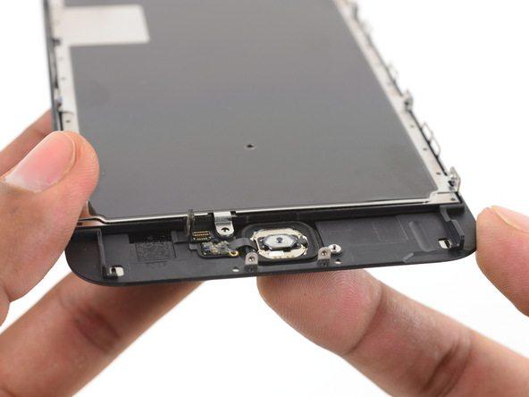 پنل جلوی آیفون 6S Plus تعمیری را مثل عکس در دستتان بگیرد. انگشت اشاره دست دیگرتان را به زیر پنل برده و روی دکمه هوم گوشی قرار دهید. به آرامی دکمه هوم را به سمت داخل هول دهید و با آن بازی کنید تا این دکمه و لاستیک اطرافش کمی از جایگاهشان بلند شوند.