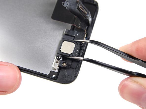 با پنس دو طرف اسپیکر مکالمه آیفون 5S تعمیری را گرفته و به سمت داخلی پنل هول دهید تا کاملا از درب پشت گوشی آزاد شود.