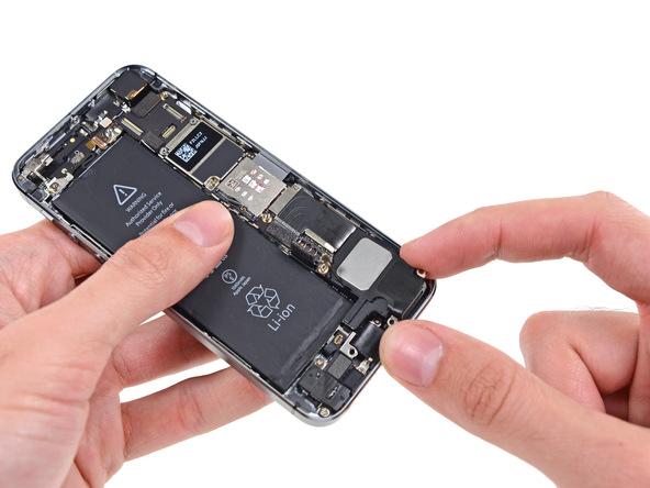 لبه زیرین اسپیکر آیفون 5S تعمیری را با انگشت بگیرید و به سمت پایین هدایت کنید تا لبه فوقانی اسپیکر به سمت بالا هدایت شود. سپس اسپیکر را به سمت راست بکشید تا کاملا از درب پشت آیفون 5S آزاد گردد.