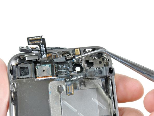 به نوک پنس سیم دکمه پاور آیفون 4 تعمیری را گرفته و خیلی آرام و با حوصله آن را از روی قاب گوشی جدا کنید.