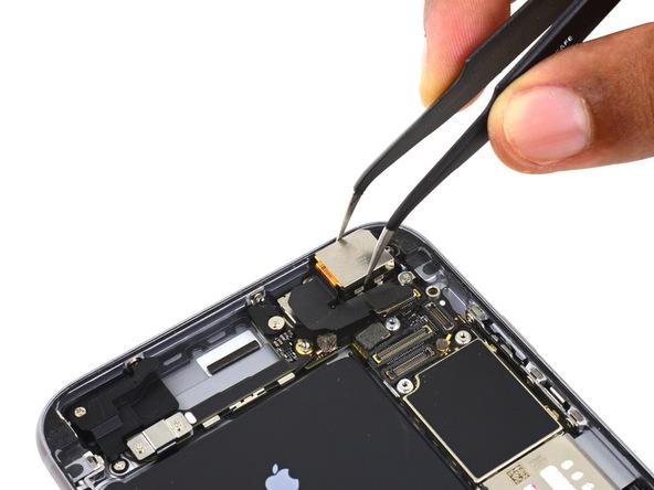 لنز دوربین اصلی آیفون تعمیری را با پنس گرفته و از پنل پشت گوشی جدا نمایید.