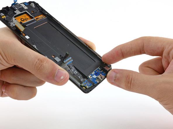 لبه سمت راست مجموعه سوکت شارژ گلکسی S6 Edge را با انگشت گرفته و به سمت بالا بکشید تا از روی بدنه گوشی بلند شود.