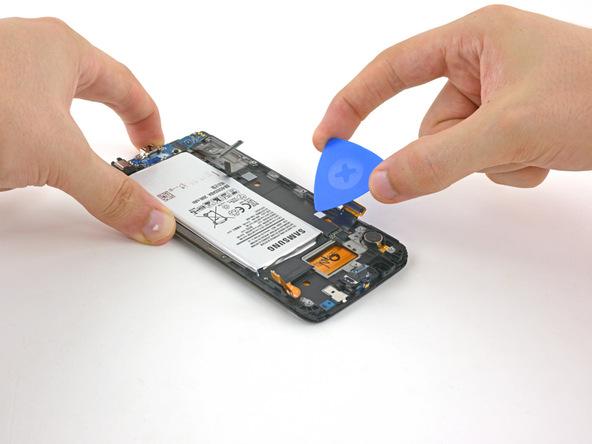 نوک پیک یا قاب باز کن کارتی را به آرامی در زیر باتری Galaxy S6 Edge تعمیری فرو برده و سعی کنید آن را از روی بدنه گوشی بلند نمایید.