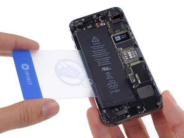 با استفاده از یک کارت شیشهای یا پیک ضخیم و فرو کردن آن در لبه سمت چپ باتری آیفون Se سعی کنید که آن را از روی جایگاهش بلند نمایید.