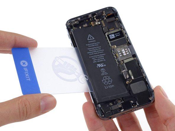 یک قاب باز کن کارتی را از سمت چپ به زیر باتری آیفون 5S تعمیری فرو برده و سعی کنید آن را از روی درب پشت گوشی بلند نمایید.