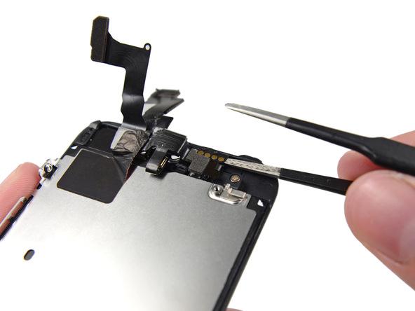 پنس را به آرامی و مثل عکس ضمیمه شده به زیر کنتکت اسپیکر مکالمه آیفون 5S تعمیری فرو ببرید تا این قطعه کمی از روی درب پشت گوشی بلند شود.