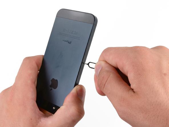 سوزن باز کننده سیم کارت آیفون 5 را در مجرای روی لبه سمت راست قاب گوشی فرو ببرید.