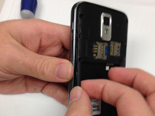 گوشی Galaxy S2 T989 تعمیری را مثل عکس اول در دستتان بگیرید یا آن را روی میز کارتان قرار دهید. نوک اسپاتول یا انگشت خود را در لبه سمت چپ قاب گوشی قرار داده و خیلی آرام سعی کنید فریم میانی آن را از روی بدنه گوشی بلند نمایید.
